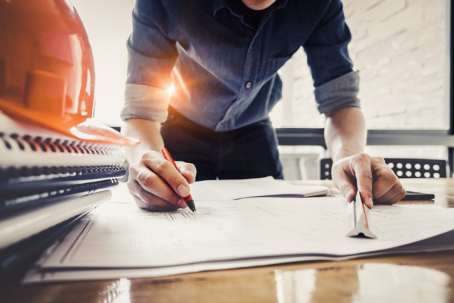 Specialized Business Insurance - View of Contractor Drawing Plans on Desk for New Building Project