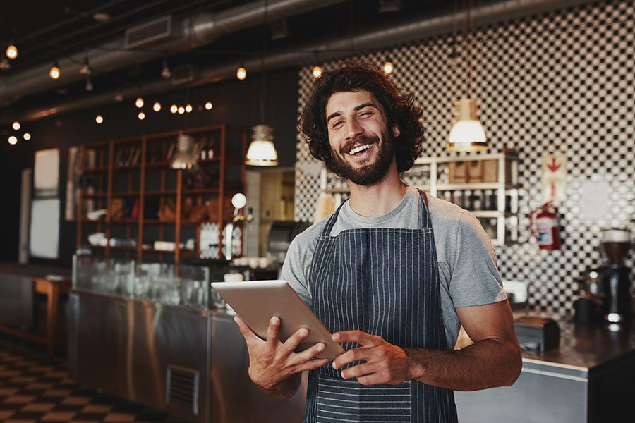 Business Insurance - Portrait of Smiling Restaurant Owner with a Tablet