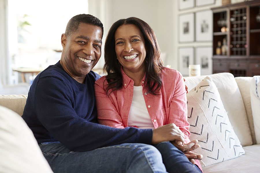 Personal Insurance - Portrait of Smiling Mature Couple Sitting in the Living Room at Home