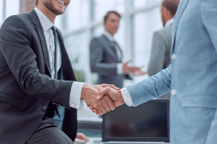 About Our Agency - Young Businessman Shaking Hands with His New Insurance Client