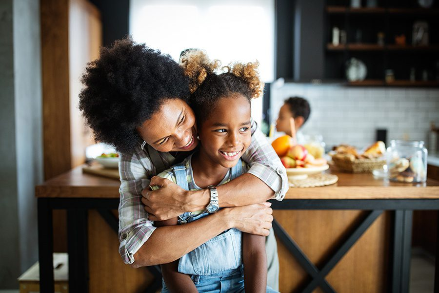 Personal Insurance - Happy Mother Embracing Her Child in the Kitchen