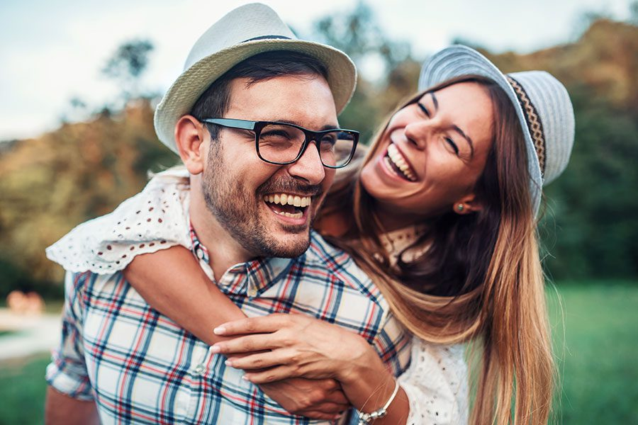 Personal Insurance - Husband and Wife Hugging and Smiling in Field