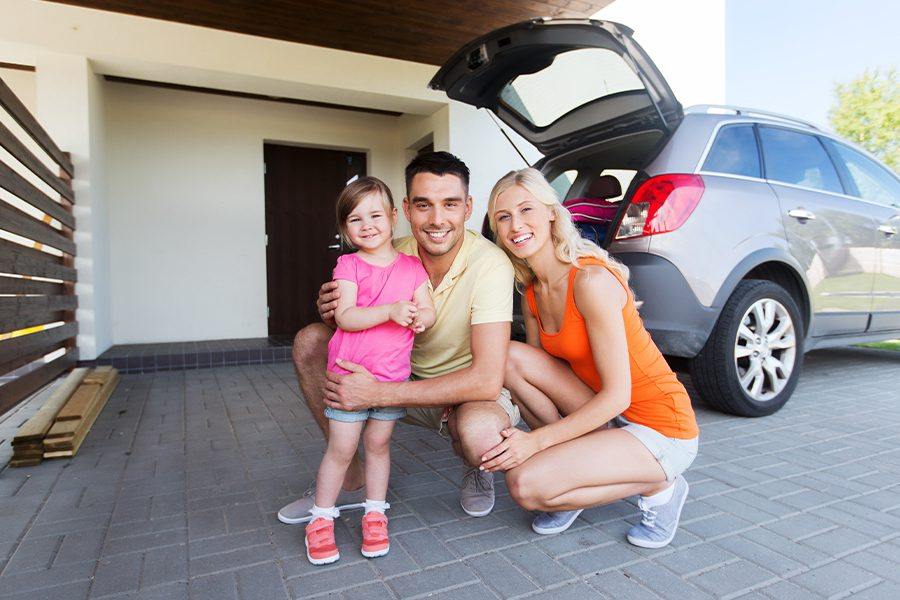 Personal Insurance - Happy Family with a Hatchback Car in Front of Home