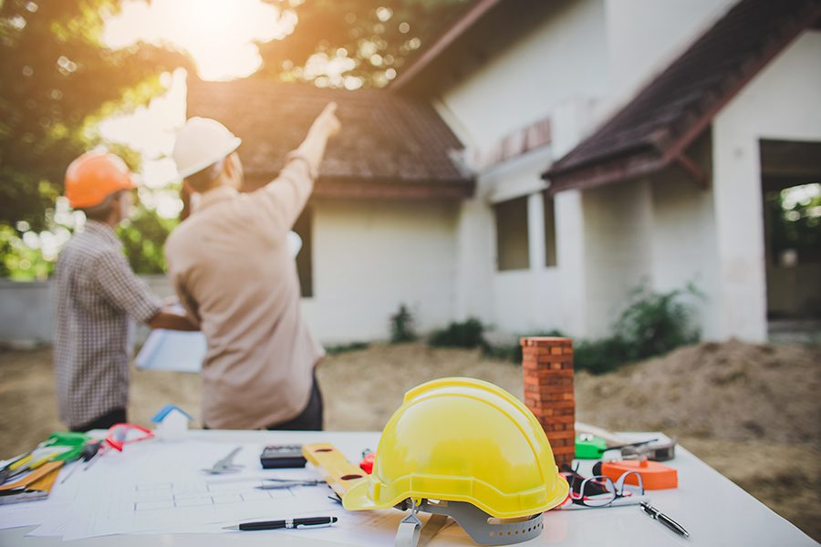Specialized Business Insurance - Engineer Pointing and Inspecting the Workplace for an Architectural Plan with Sun Showing Through the Trees