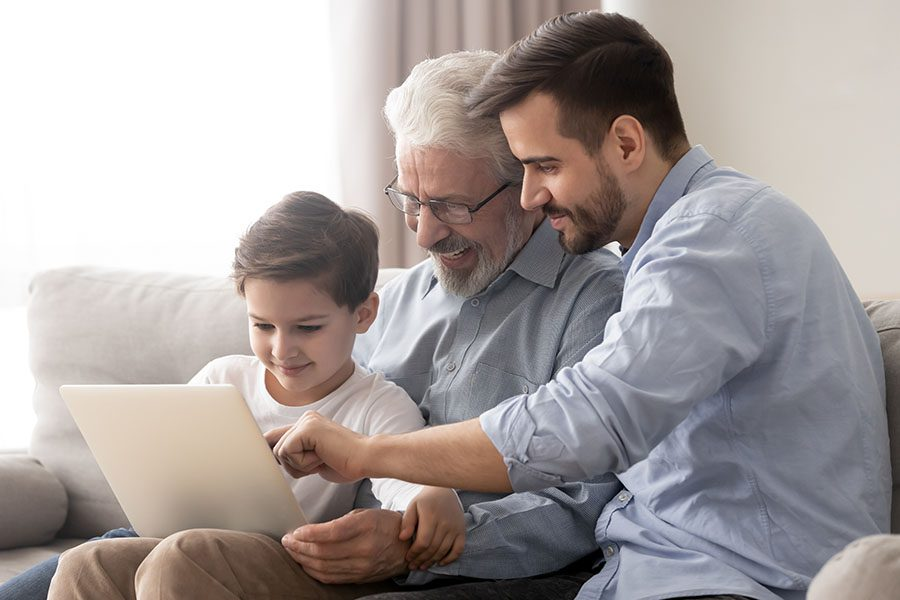 Blog - Father Son And Granfather Sitting On Couch Using The Laptop