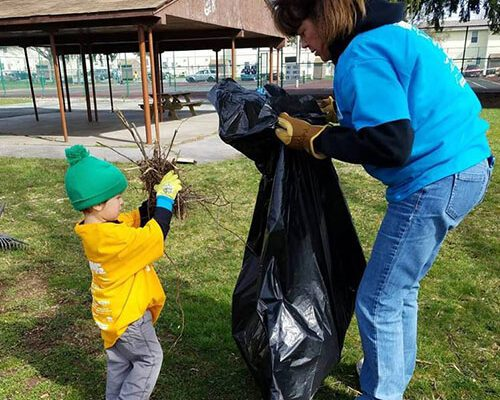 Community - Strickler Insurance Team Member Cleaning Up In The Community With Young Boy