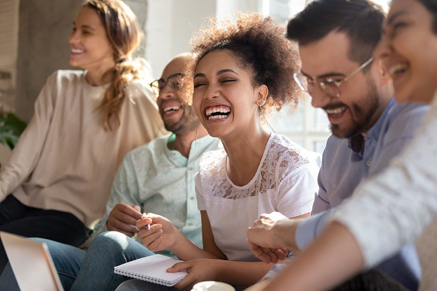 Employee Benefits - Group Of Employees Sitting In Office During Meeting Laughing And Smiling
