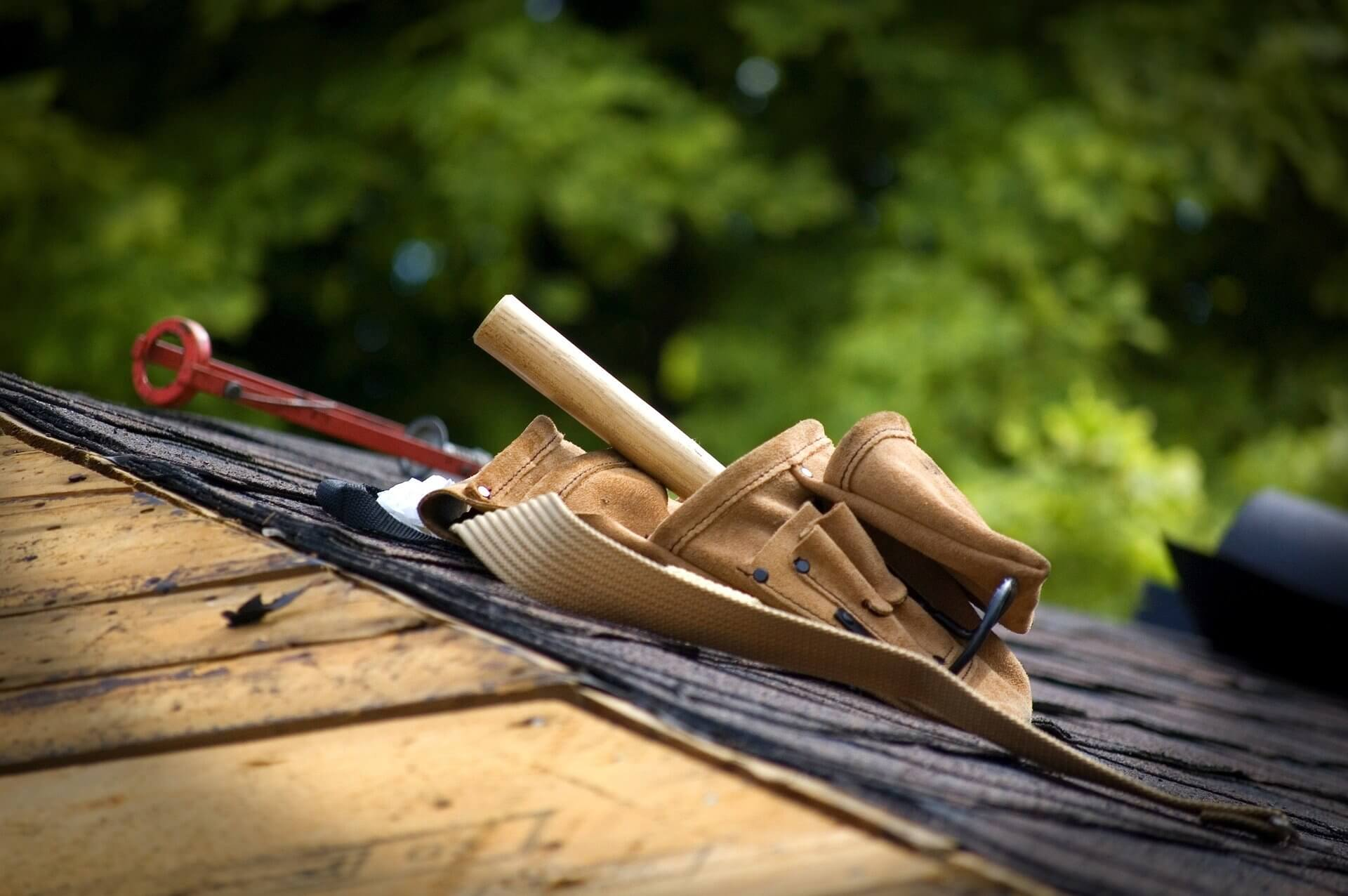 Stock image of a toolbelt on a shingled roof.