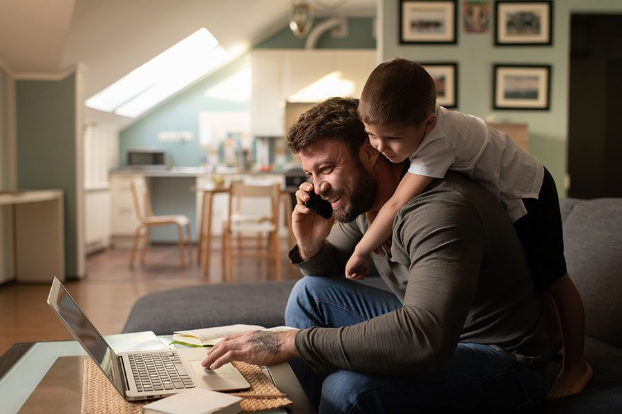 Contact - Father Happily Using a Laptop and Cell Phone While Son Hangs on His Back