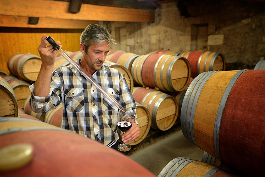 Specialized Business Insurance - Winemaker Tests Supply in Storage Room Surrounded by Barrels of Wine, Holding a Glass of Red Wine