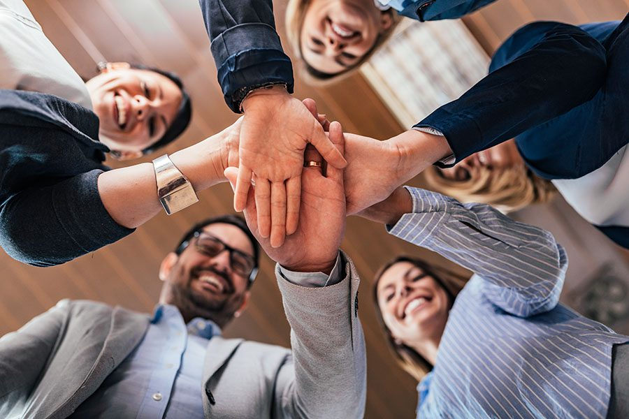 Insurance Quote - Group of Smiling Employees at the Office Joining Their Hands Together