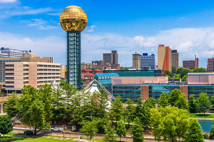 About Our Agency - Downtown Knoxville, Tennessee Skyline on a Sunny Day with Trees in the Foreground