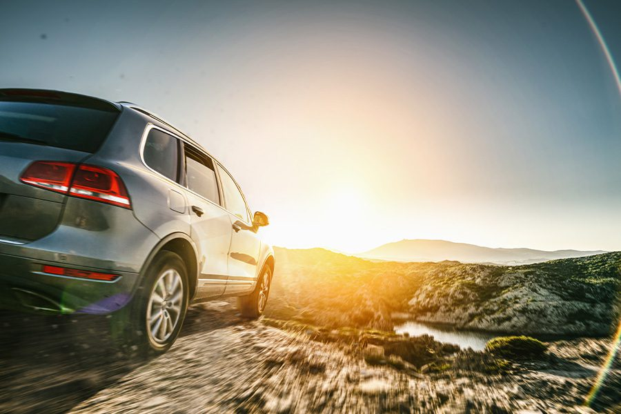 Personal Insurance - Closeup View of an SUV car in Mountain Landscape at Sunset