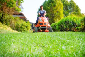 Blog - Gardener driving a riding lawn mower in garden