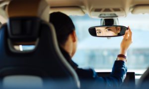 Technology Helps Identify, Reward Safe Drivers - Woman in Car Checking Mirrors and Driving Safely