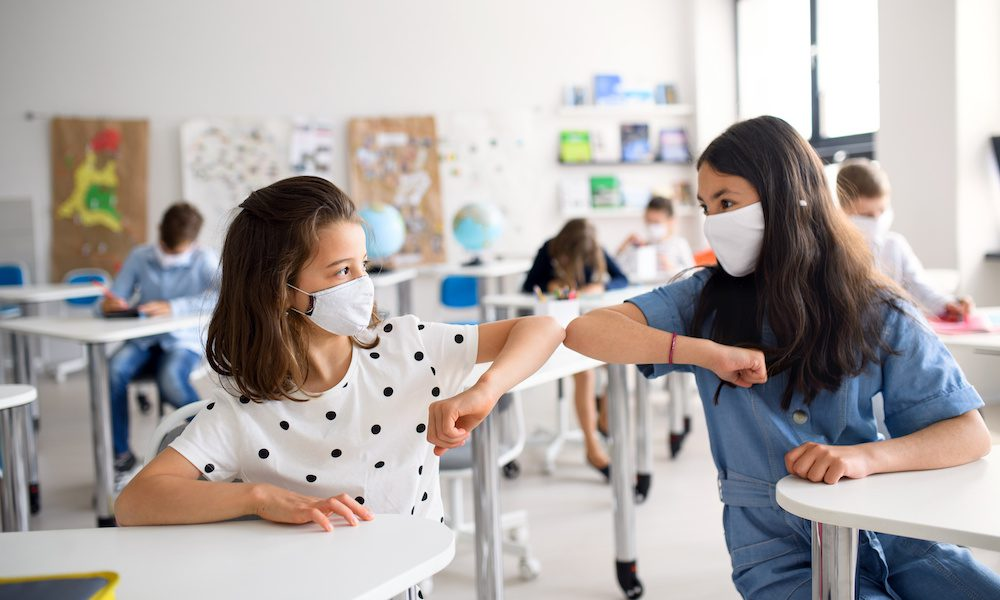 Two girls wearing masks sitting in class and bumping elbows