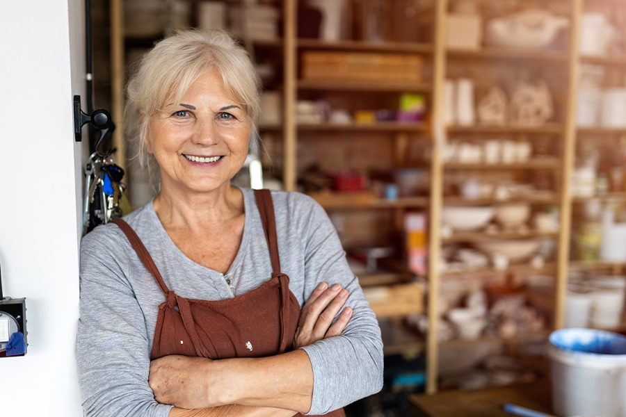 Business Insurance - Portrait of Older Female Artist in Front of Her Small Business Art Studio