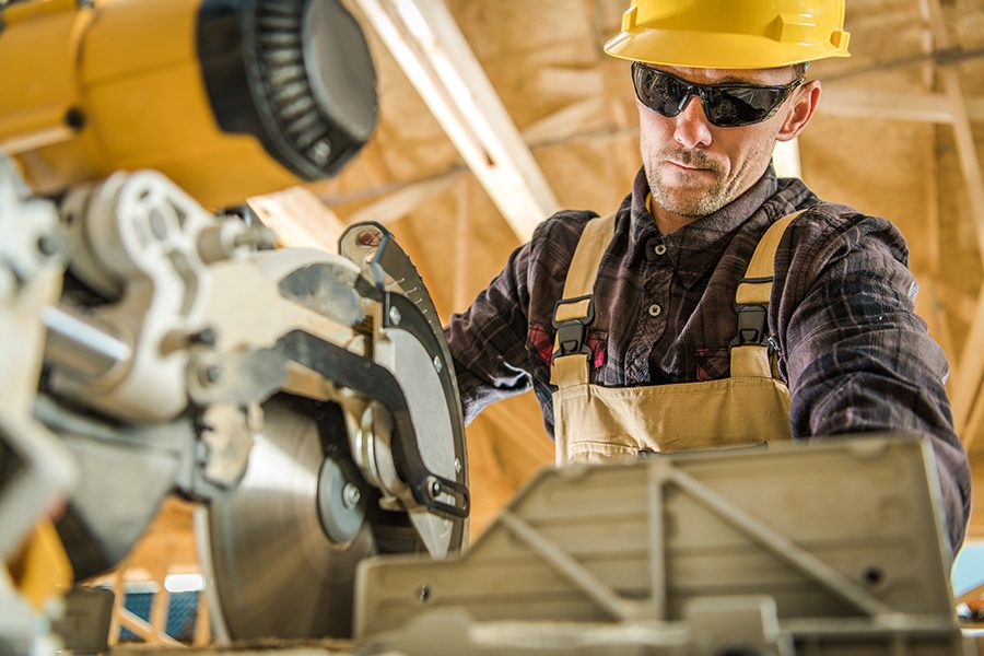 Specialized Business Insurance - View Looking Up at Construction Contractor Working With Power Saw