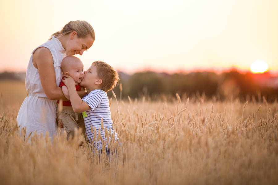 Blog - Family Exchanging Kisses in a Wheat Field