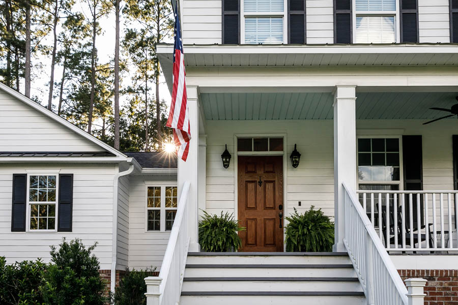 Personal Insurance - Modern White Farmhouse with a Proud American Flag Out Front