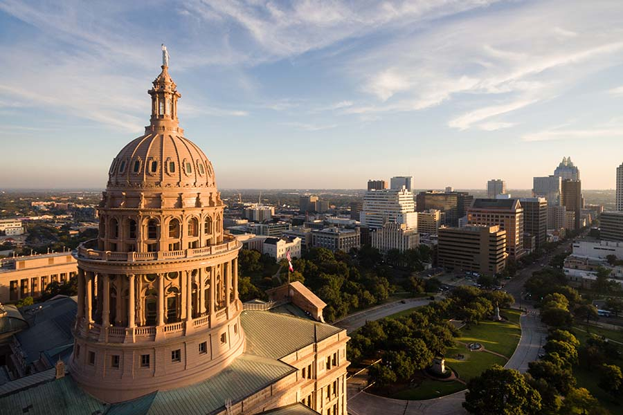 About Us - Ornate Texas State Capitol Building Shining at Sunset, With Green City Parks, Flags Flying, and Tall Buildings Below