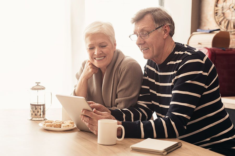 Blog - Senior Couple at Their Kitchen Island Sharing Scones and French Pressed Coffee While Reading a Tablet Together