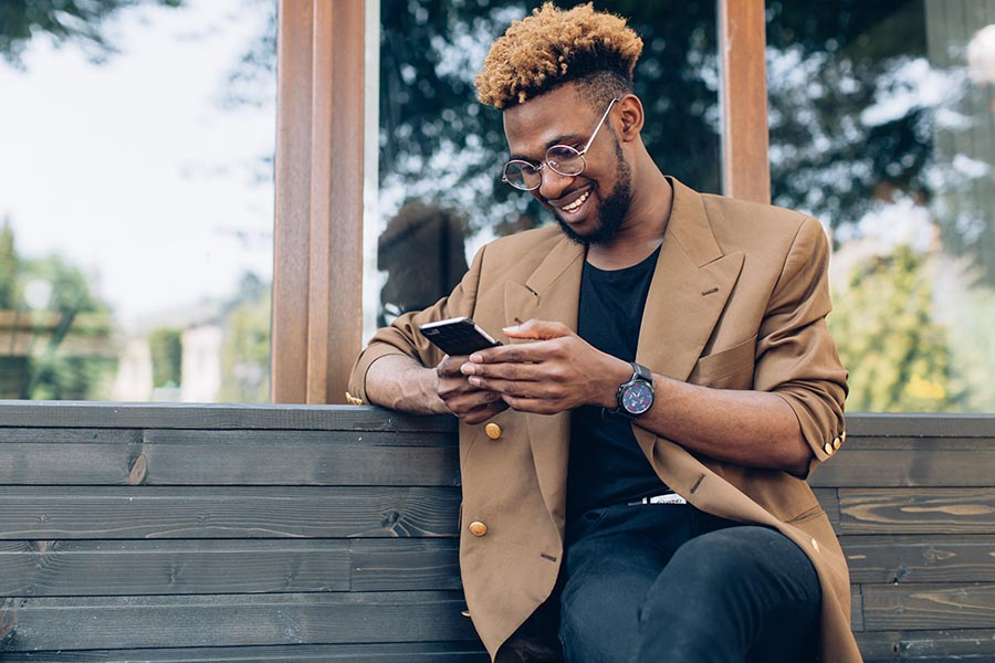 Contact Us - Stylish Young Man With Beard and Glasses on a Wooden Bench Using His Cell Phone
