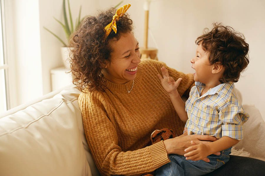 Personal Insurance - Mother and Toddler Son With Brown Curly Hair Laughing on a Leather Sofa in Their Living Room With Plants Behind Them