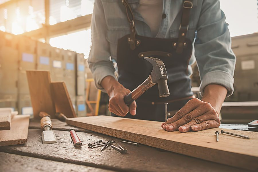 Specialized Business Insurance - Carpenter Preparing to Hammer a Nail Into a Long Board With Sunlight Streaming Into Their Workshop