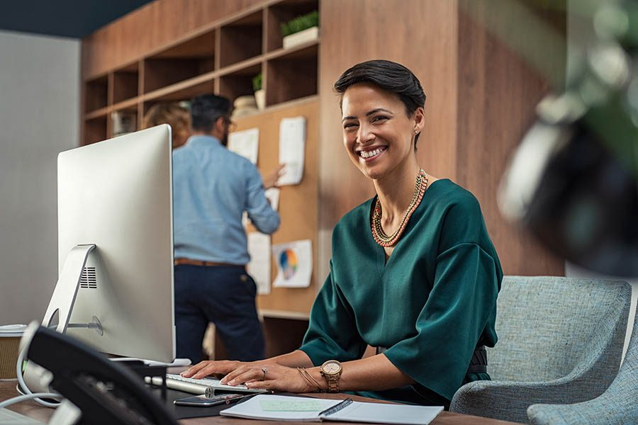 Business Insurance - Businesswoman in Green Blouse Smiles and Uses Her Computer at Her Desk in a Bustling Law Office