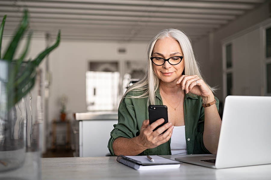Client Center - Senior Woman With Long White Hair and Fashionable Glasses Uses Laptop and Smartphone at a Desk in a Bright White Office