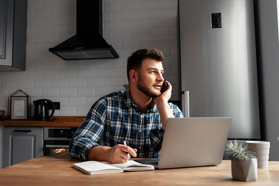 Contact Us - Young Man in Plaid Shirt Takes Notes on a Phone Call in His Gray and White Kitchen With Laptop and Potted Plant at His Kitchen Table
