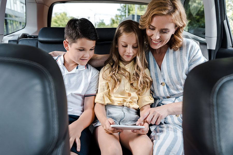 Client Portal - Mother And Two Kids Sitting In Car Using Tablet