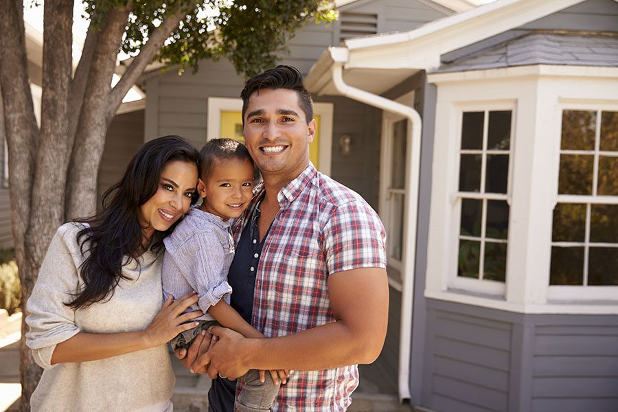 Personal Insurance - Younbg Family Holding Their Child Standing Outside Their Home