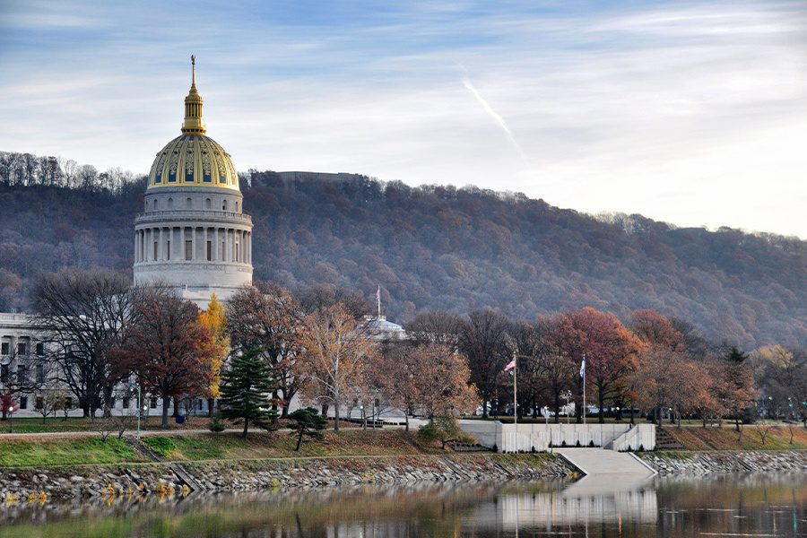 Charleston, WV Insurance - West Virginia Capitol Building in the Background with a River and Autumn Colored Trees and Hill on a Fall Day