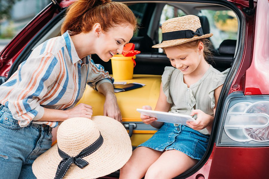 Personal Insurance - Mother tending to her Daughter while Sitting in the Back of the Car on a Family Vacation