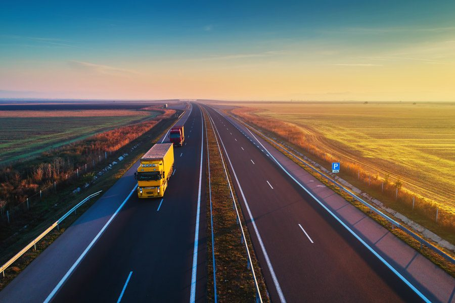 Business Insurance - Trucks Driving Along a Highway Next to Farmland at Sunset