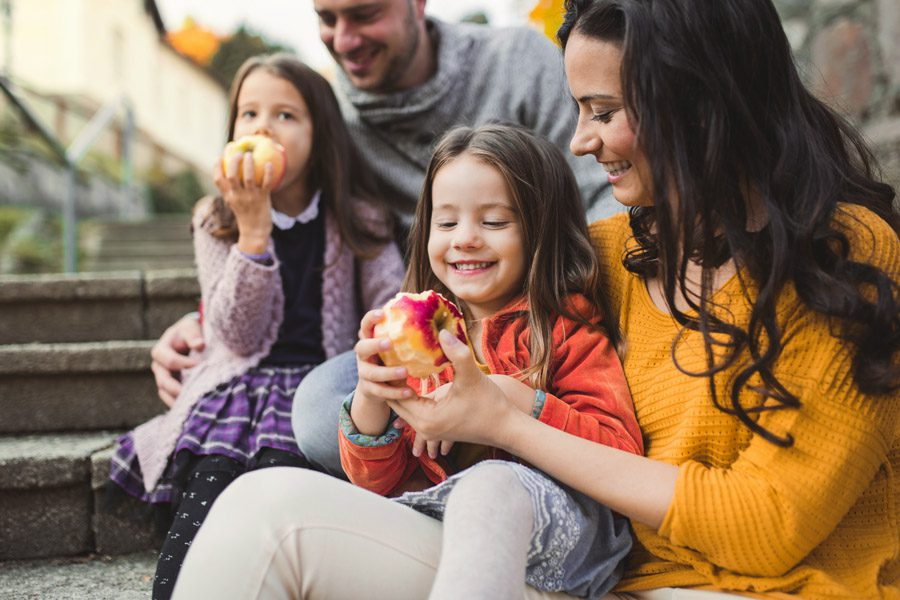 Client Center - Happy Family Eating Apples on the Front Stoop