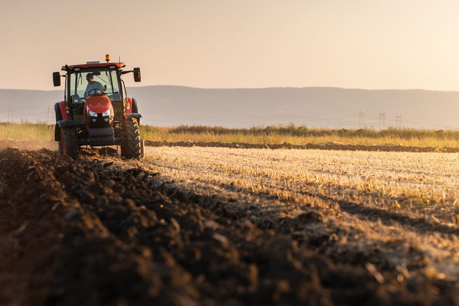 Farm Insurance - Farmer Plowing His Land ay Daybreak in a Red Tractor