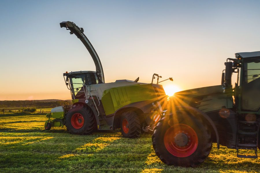 Specialized Business Insurance - Tractor Plowing During the Summer at Sunrise