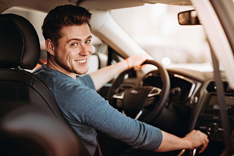 Add or Remove Driver - Man Driver Turning Around and Smiling in Drivers Seat