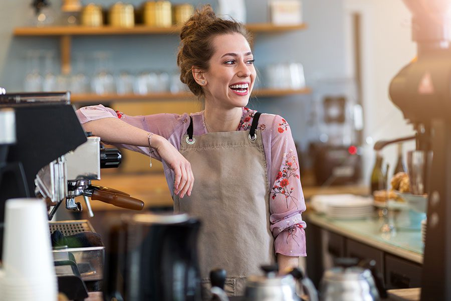 Business Insurance - Woman Coffee Shop Worker with Apron Smiling