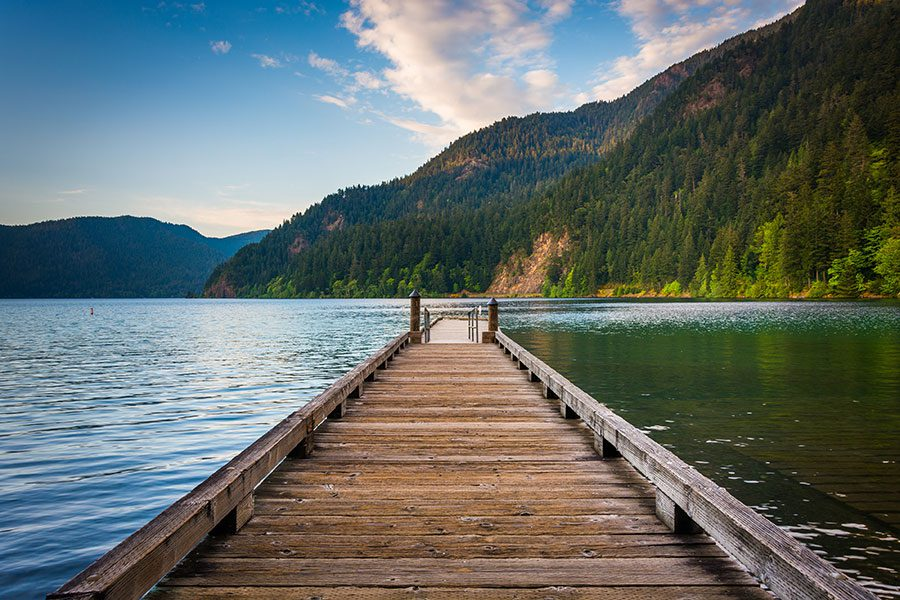 Port Angeles WA Insurance - Wooden Dock Extending into Water with Green Mountains and Blue Sky