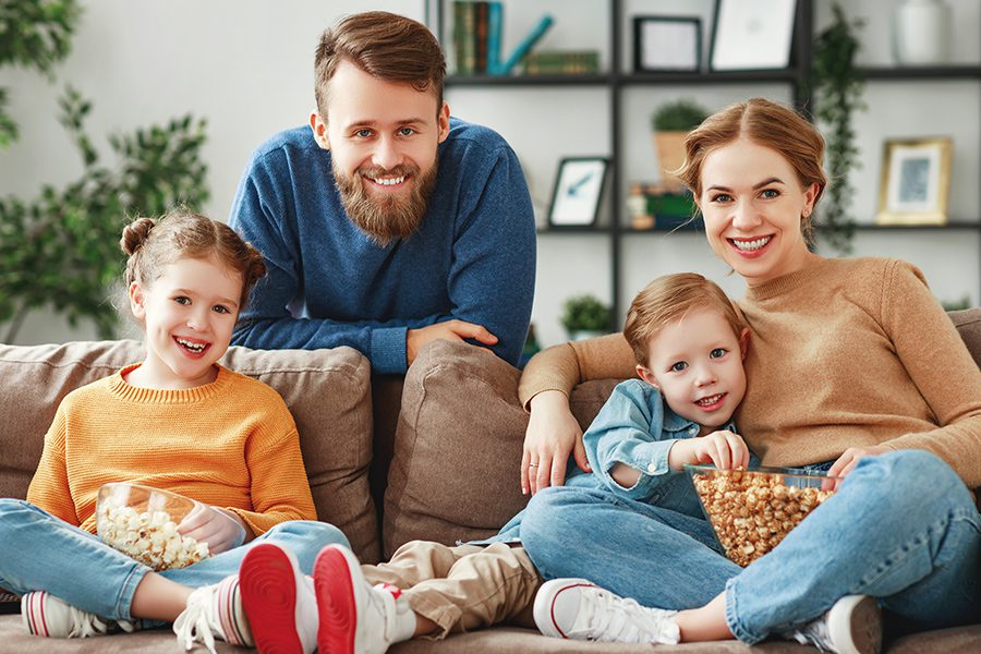 Personal Insurance - Joyful Family Resting on Sofa Together
