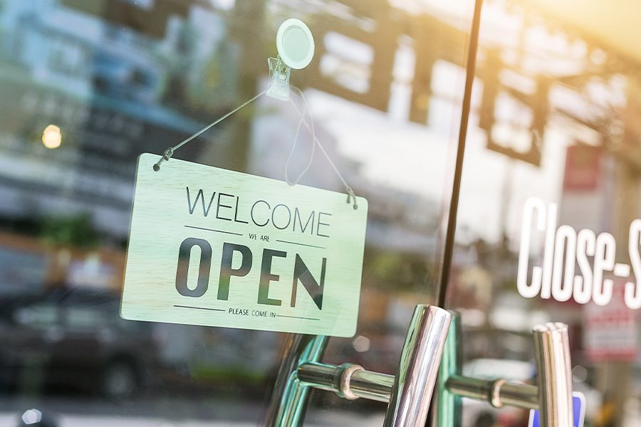Business Insurance - Closeup of Store Front Door and Handle with Open Sign and Steet View Reflected on Glass