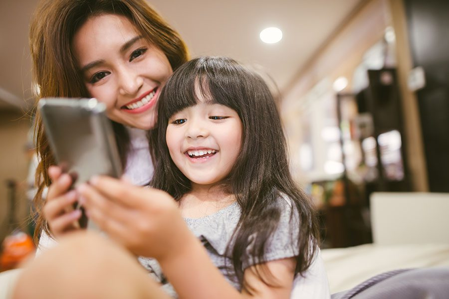 Contact - Smiling Asian Mother And Daughter Using Cellphone