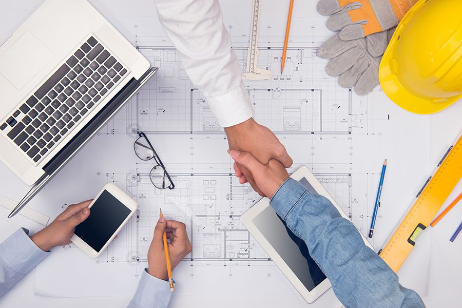 Specialized Business Insurance - Hands Of Professional Contractors Discussing Blueprints