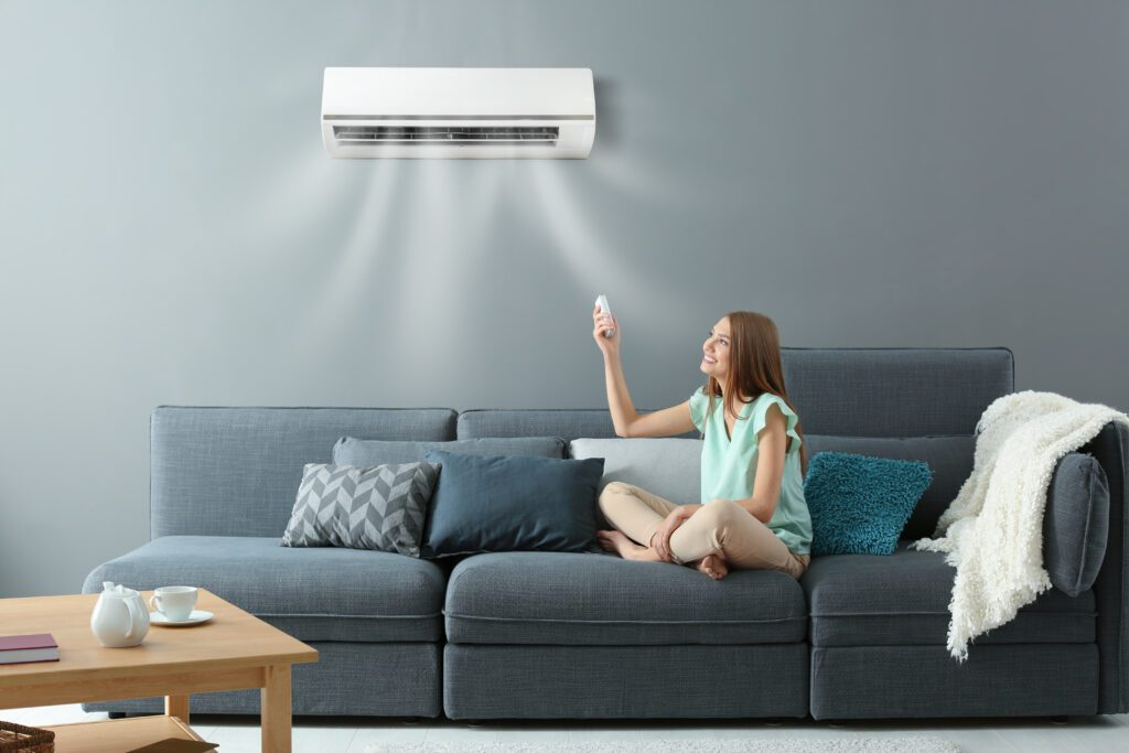 A girl sitting at home with the air conditioner.