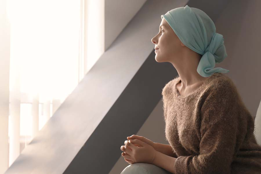 Accident and Critical Illness Insurance - A Woman with Cancer Sitting and Looking Out a Hospital Window