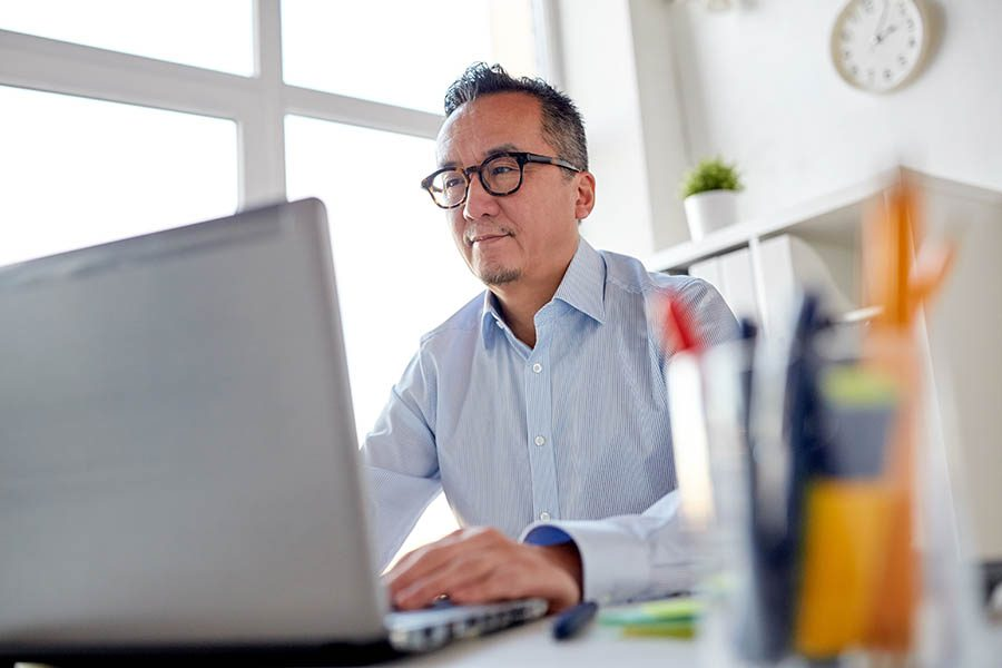 Blog - Middle-Aged Man in Dress Shirt and Tortoiseshell Glasses Reads on His Laptop in a Modern, Clean White Office